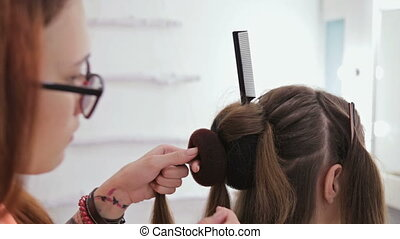 Close up shot. Professional hairdresser doing hairstyle for young pretty woman