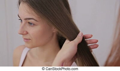 Close up shot. Professional hairdresser doing hairstyle for young pretty woman with long hair