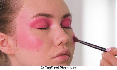 Close up shot. Professional make-up artist applying eyeliner...