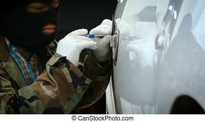 Close up shot Thief stealing the car using tool to open car...