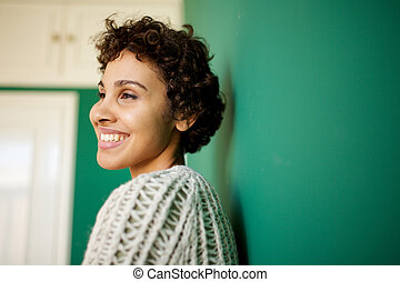 Close up side of african american woman smiling against green wall