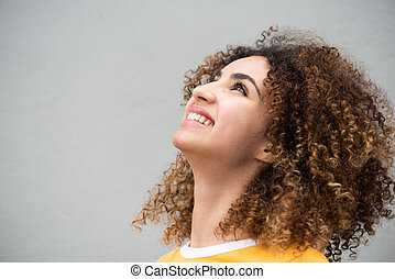 Close up side of beautiful young african american woman smiling and looking up