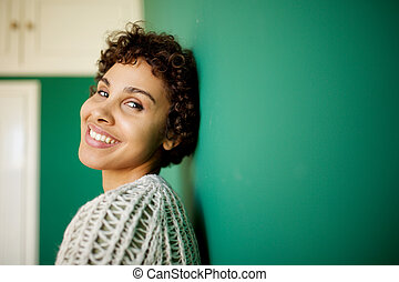 Close up side of happy african american woman smiling against green wall