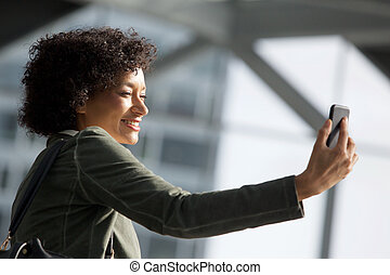 Close up side of happy african american woman with cellphone