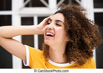 Close up side of smiling young african american woman with hand in curly hair