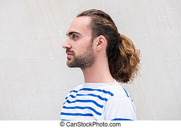 Close up side of young man with long hair in ponytail by white background