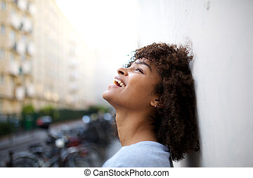 side portrait of beautiful smiling young african american woman leaning against wall outside