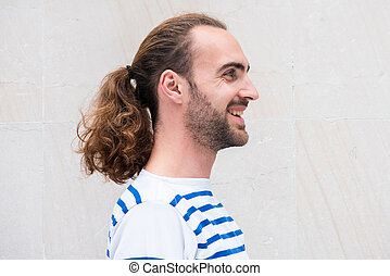 side portrait of young man with long hair in ponytail smiling by white background