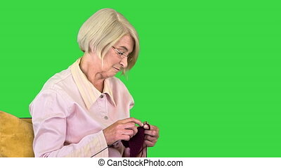 Close up. Side view. Cheerful elderly woman knitting and listening to a person behind the camera on a Green Screen, Chroma Key. Professional shot in 4K resolution. 063. You can use it e.g. in your medical, commercial video, business, presentation, broadcast