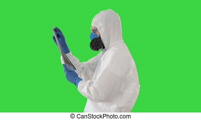 Close up. Side view. Epidemiologist in respirator examine the patient's pneumonia on a radiograph Covid-19 on a Green Screen, Chroma Key. Professional shot in 4K resolution. 53. You can use it e.g. in your medical, commercial video, business, presentation, broadcast