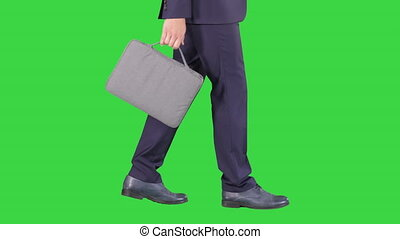 Handsome businessman in a suit walks with a briefcase on a...