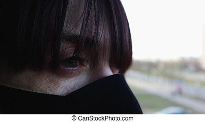 Close-up side view of a young woman in a protective mask. ...