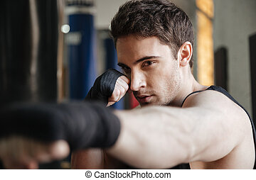 Close up side view of boxer training in gym
