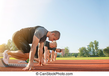 Close-up side view of cropped people ready to race on track field