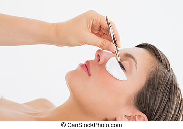 Close-up side view of hand plucking eyelashes over white background
