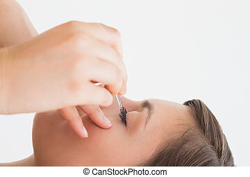 Close-up side view of hand plucking eyelashes over white...