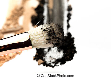 Close-up side view of professional make-up brush with natural bristle and black ferrule with crashed eyeshadow isolated on white background