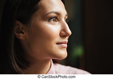 Close up side view of smiling brunette woman looking away