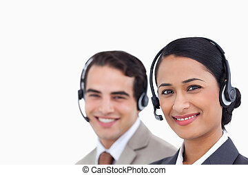 Close up side view of smiling telephone support employees at work against a white background
