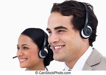 Close up side view of smiling telephone support employees