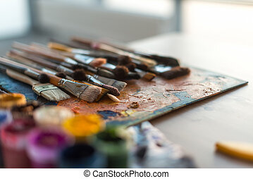 Close-up side view picture of a wooden paintbrush collection lying on old palette and gouache set in the workroom with natural light.