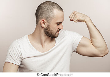 close up side view portrait of a muscular young man showing his biceps