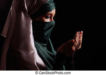 close up side view shot of pleasant Muslim girl in praing pose