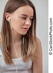 close up side view shot of romantic woman in earphones