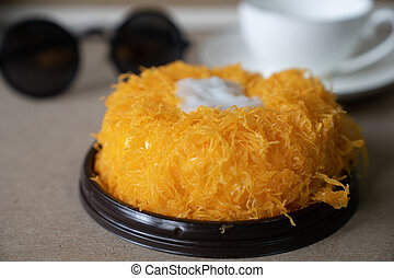 """close up side view soft focus Gold Egg Yolk Thread Cakes, or 'Cake Foi Tong"""" Thai cake with blurred white coffee cup in background copy space"""