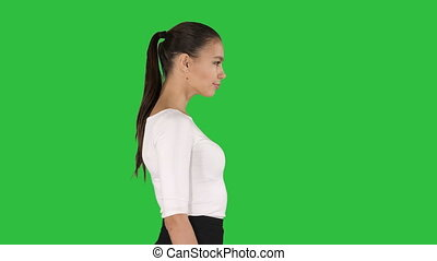 Young business woman is walking on a Green Screen, Chroma Key.