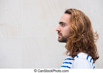 Close up side young man with long hair and beard by white background