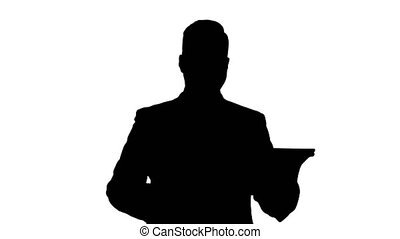 Silhouette Handsome man swiping pages on tablet and smiling...