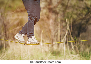 Slacklining is a practice of balancing, in which nylon or polyester fabric stretched between two anchor points is commonly used. People walk on it and do tricks