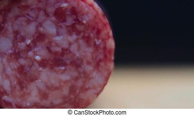 Slices of sausage roll to the side. Pieces of salami the dark background.