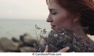Close-up. Slow motion. Girl with flowers on the beach with a beautiful appearance
