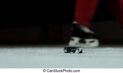 Close-up slow motion hockey puck and flying snow on the ice...
