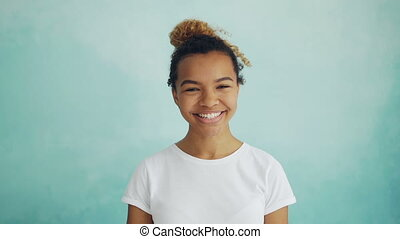 Close-up slow motion portrait of cheerful young woman with...