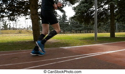 Close-up slow motion shot of a man legs jogging on the course track