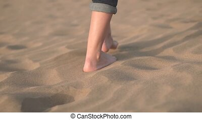 Close up, Slow motion. Woman feets walking on golden sand at...