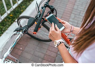 Close-up smartphone girl's hands. In summer city background parking for bicycles, girl chooses route in application, Internet online map on phone. The route of bike path. Bicycle parking in city.