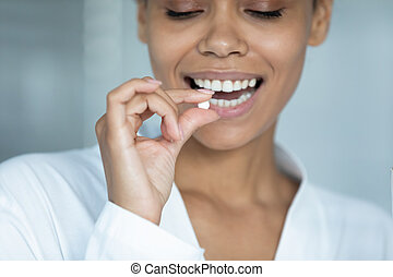Close up smiling African American woman holding white round pill