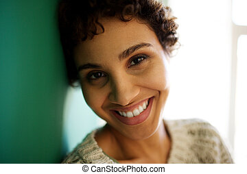 Close up smiling african american woman leaning against wall