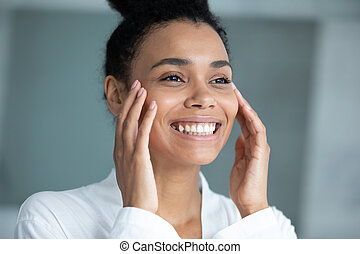 Close up smiling African American young woman touching face