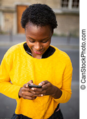 Close up smiling african woman looking at mobile phone ion city