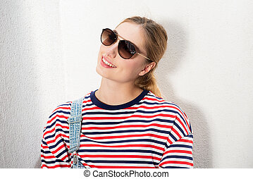 Close up smiling blond girl with sunglasses by white background