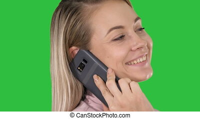 Smiling blonde talking on the phone on a Green Screen, Chroma Key.