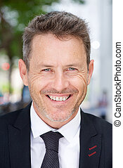 Close up smiling businessman standing outside in suit and tie