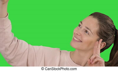Smiling cheerful blond-haired woman doing selfie on a Green...