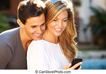 Close up smiling couple sitting outside looking at smart phone