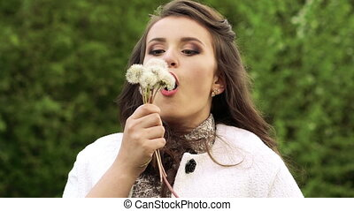 Close up smiling girl blowing dandelions. Slow motion
